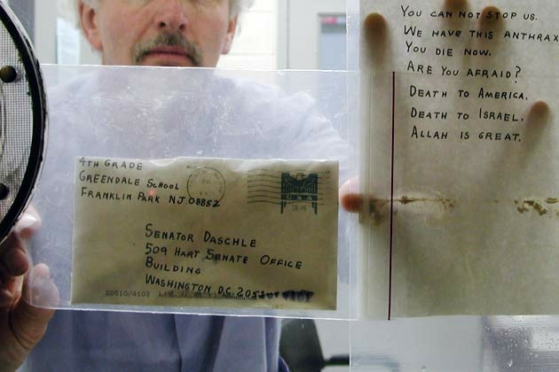 A U.S. Army scientist holds up one of the anthrax letters.