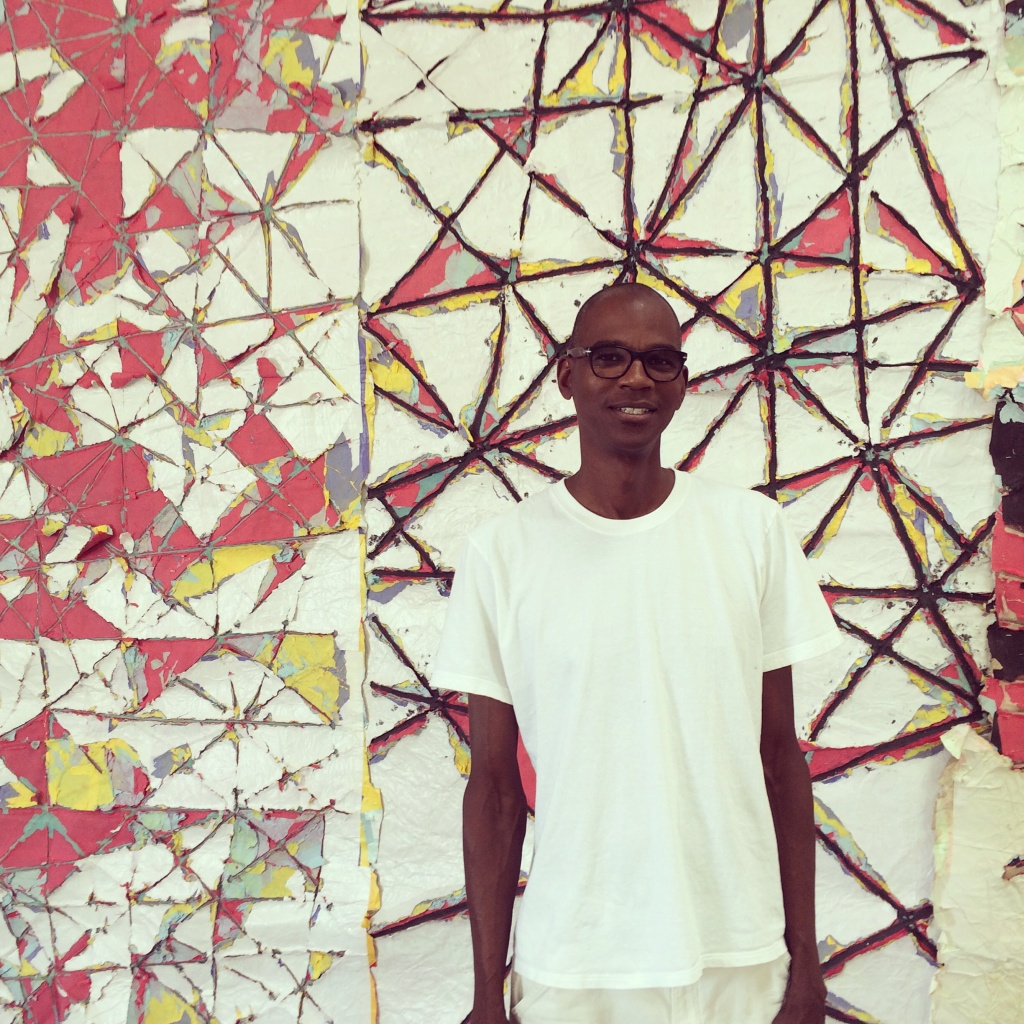 Artist Mark Bradford stands in front of a piece in his South LA studio.