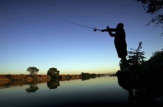 A fisherman casts his line into the Sacramento River in the Sacramento-San Joaquin River Delta south of Sacramento.