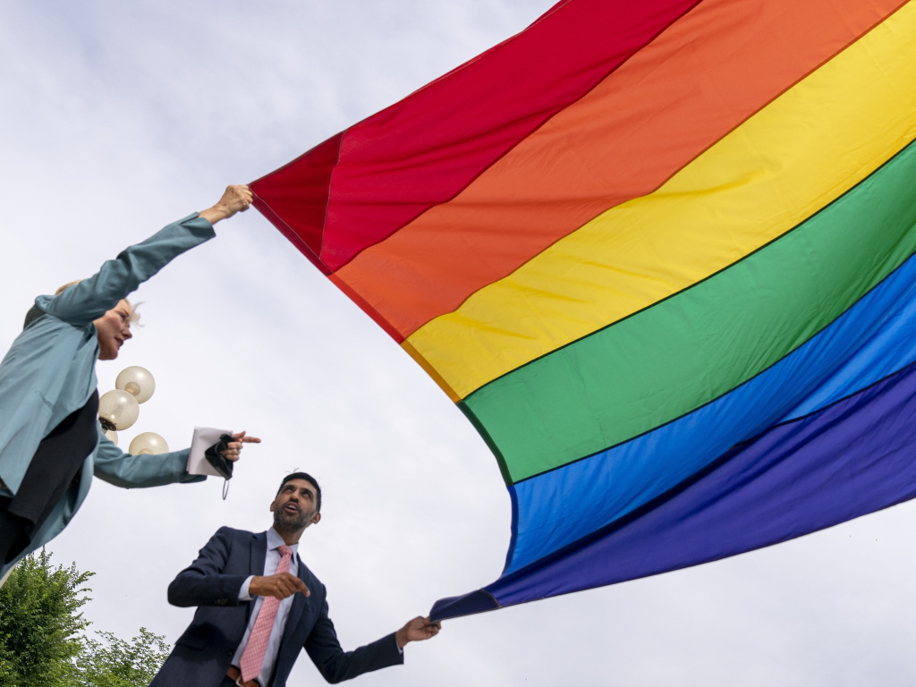 Energy Secretary Jennifer Granholm and Department of Energy Chief of Staff Tarak Shah help raise the Progress Pride Flag outside the Department of Energy in Washington, Wednesday. The Pentagon decided not to allow the flag to fly on military installations for Pride Month.