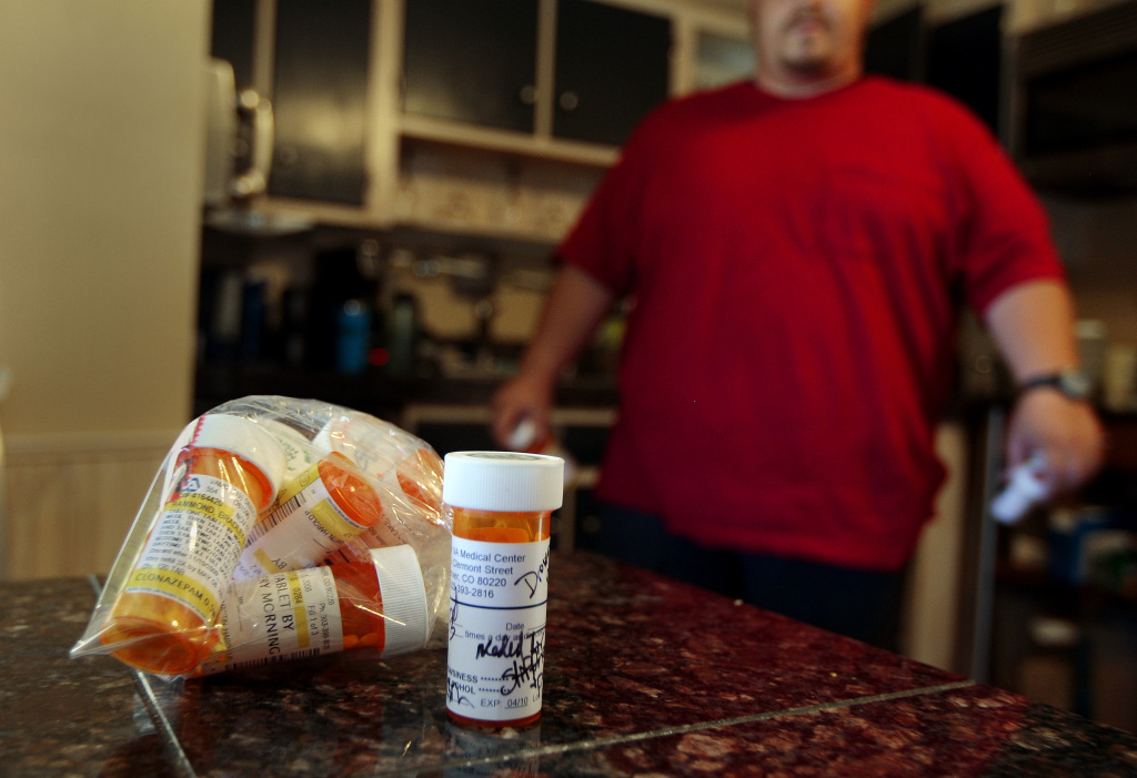 A vet walks in his kitchen near some of the many prescription drugs he has been prescribed by doctors to help him cope with his PTSD.