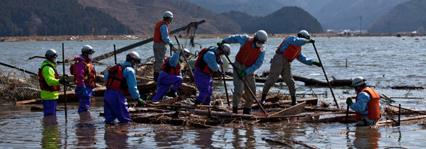 Japanese firemen pick through the rubble looking for bodies of victims of the tsunami in a flooded area of Ishinomaki in Miyagi prefecture on April 1, 2011.