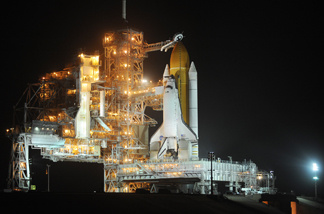 The US space shuttle Discovery is seen after the rotating service structure (L) is moved away February 23, 2011 at Kennedy Space Center in Florida as preparations are made for a February 24 launch.