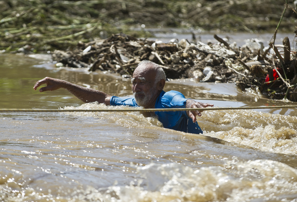 A man wades through a flooded street in Acapulco, state of Guerrero, Mexico, on September 18, 2013 as heavy rains hit the country.