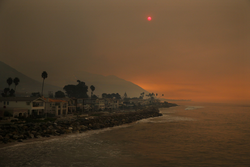 Homes stand along the beach as the sun is visible through thick smoke from a wildfire Wednesday, Dec. 6, 2017, in Ventura, Calif.