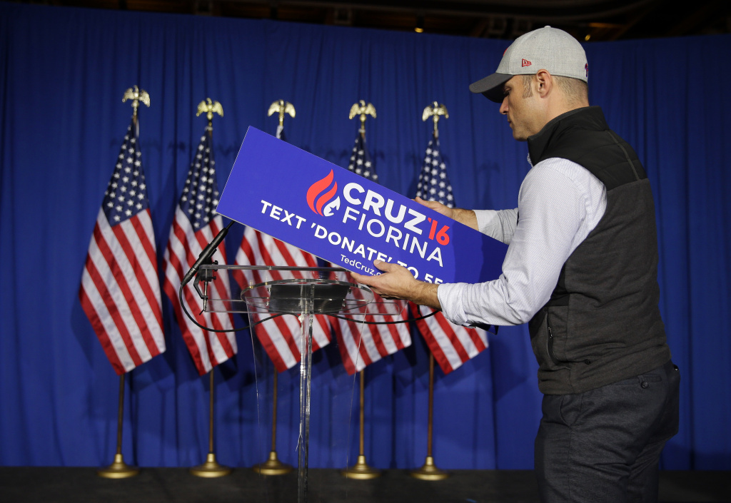 A worker for Republican presidential candidate Sen. Ted Cruz, R-Texas, removes the campaign sign from the podium following primary night campaign event in Indianapolis, Tuesday, May 3, 2016. Cruz ended his presidential campaign, eliminating the biggest impediment to Donald Trump's march to the Republican nomination. (AP Photo/Michael Conroy)