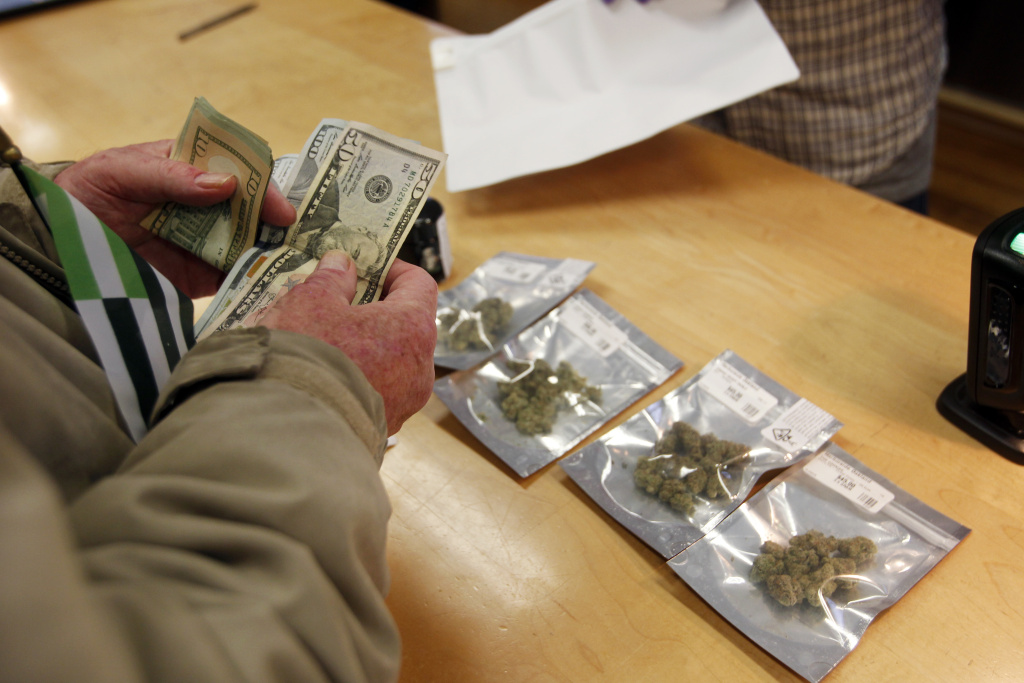 A customer purchases marijuana at Harborside marijuana dispensary, Monday, Jan. 1, 2018, in Oakland, Calif.