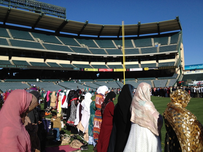 Women line up for prayer on the grass of Angel Stadium field.