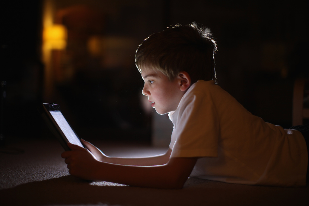 In this photograph illustration a ten-year-old boy uses an Apple Ipad tablet computer on November 29, 2011 in Knutsford, United Kingdom.