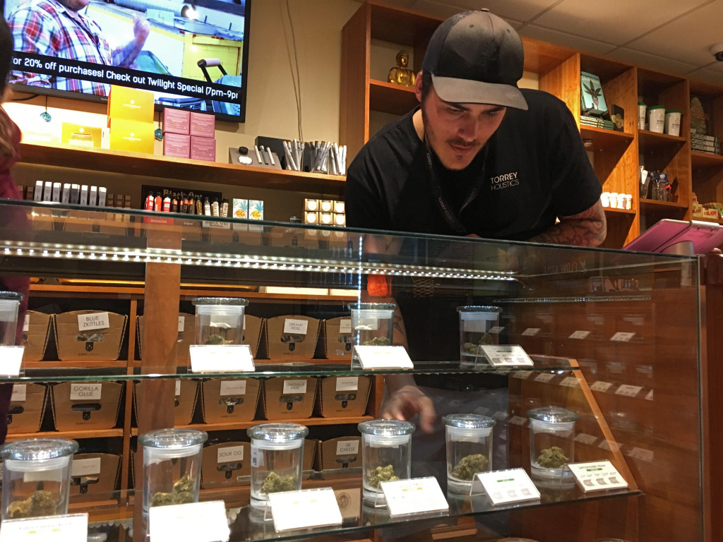 Torrey Holistics employee Taron McElroy arranges jars of cannabis in San Diego, Calif., Thursday, Dec. 14, 2017. On Thursday, the state issued its first batch of business licenses for the upcoming legal marijuana market, setting the stage for sales to begin to adults in January. The first license for recreational retail sales went to Torrey Holistics in San Diego.