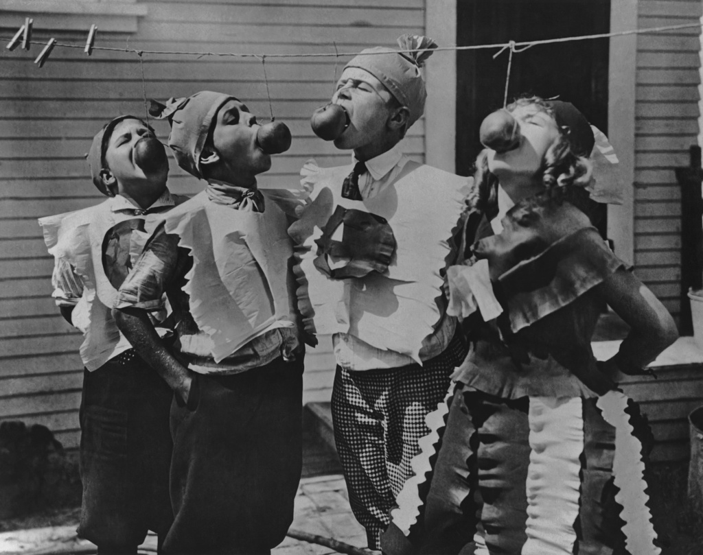 Four children attempting to bite apples on a string at a Halloween party circa 1950's.
