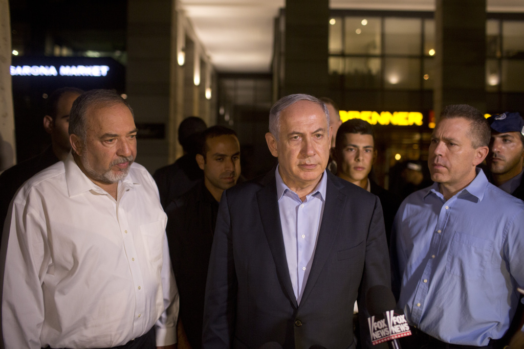 Israeli Prime Minister Benjamin Netanyahu (C) and Defence Minister Avigdor Liberman (L) speak to the press at the scene of a shooting outside Max Brenner restaurant in Sarona Market in Tel Aviv, Israel.