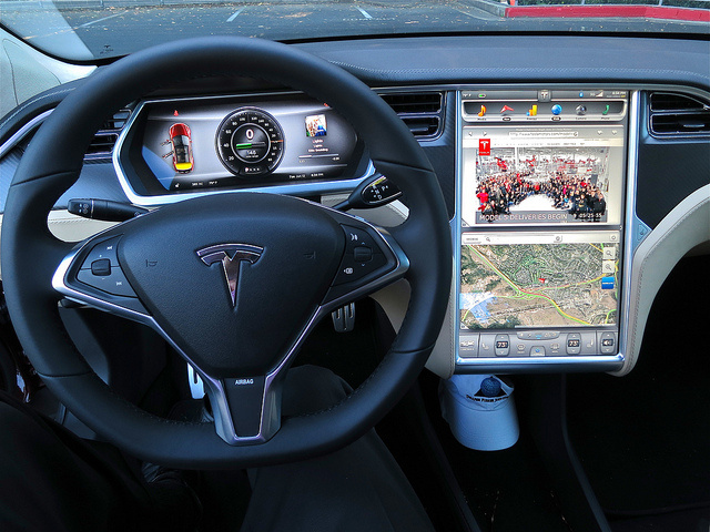 The interior of a Tesla car with displays for a web browser, Google Map view and a dashboard view that includes the odometer and a picture of the album that's being streamed from a cloud service.