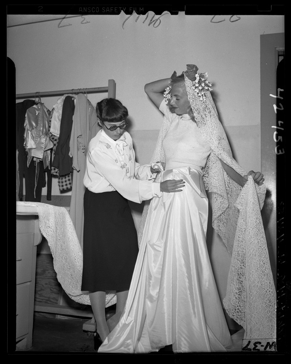 Hollywood fashion designer Edith Head working on a wedding gown for Dick Tracy comic strip's Gravel Gertie, 1946.