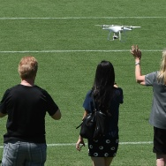 One person waves to the camera on a drone as people pose for a photo, July 3, 2016, at the Rose Bowl stadium in Pasadena, California.