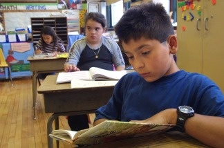 A student in Ms. Newman''s third grade class reads a book during summer school July 3, 2001 at Brentano Academy in Chicago.