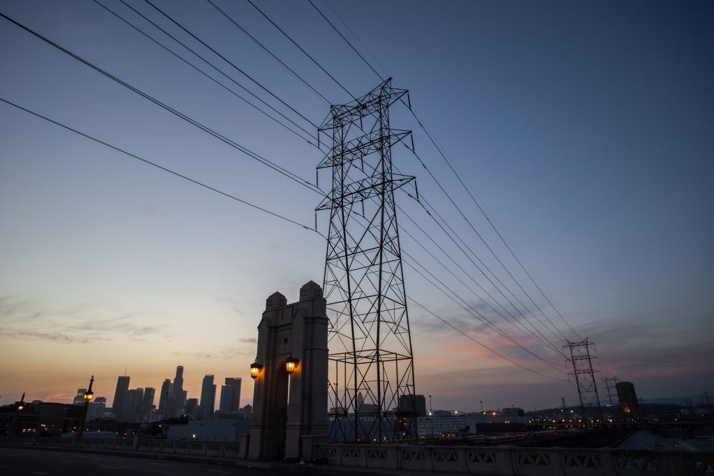 Downtown skyline is seen behind high tension towers from the 4th street bridge in Los Angeles, California on August 16, 2020.