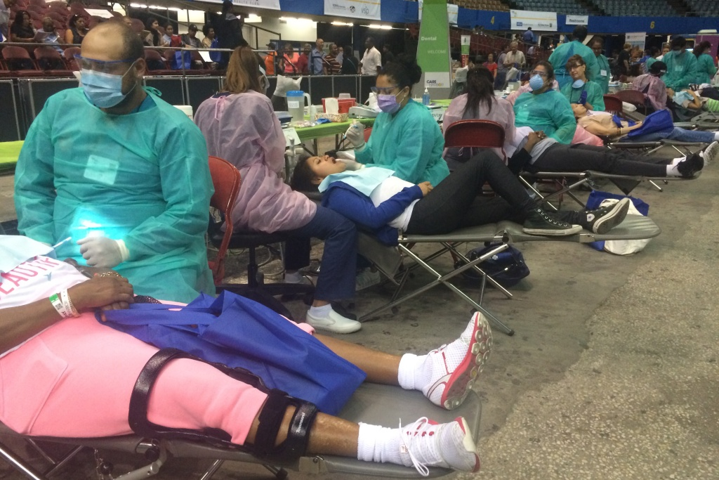 Dentists work on patients at the Care Harbor/L.A. free medical clinic at the L.A. Sports Arena.