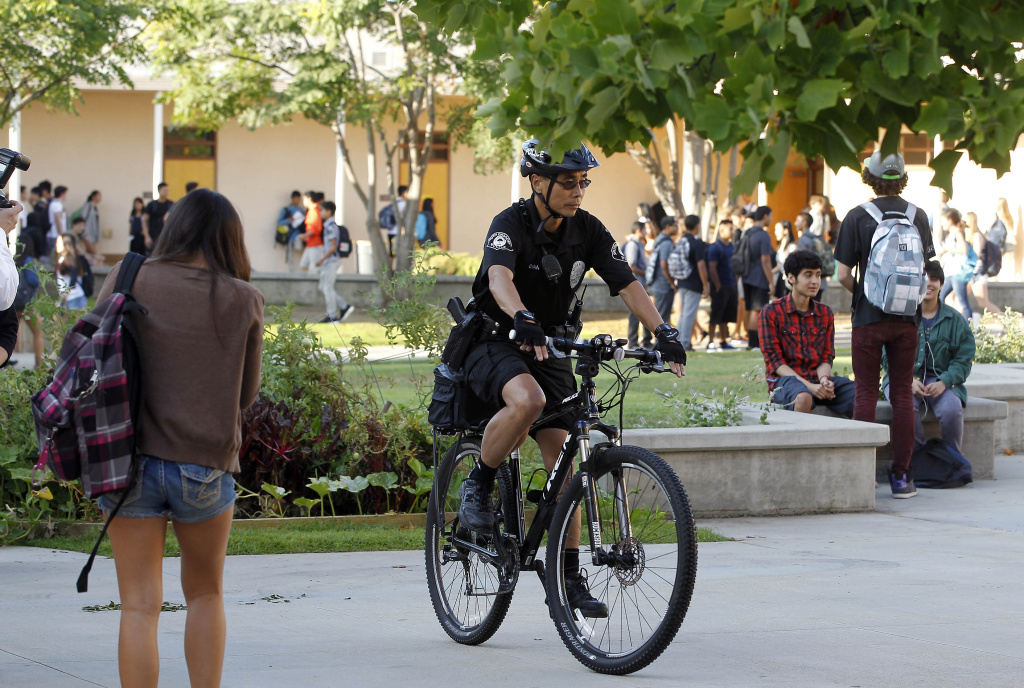 A South Pasadena police officer patrols the campus of South Pasadena High School as students arrive for the first day of school on Thursday, Aug. 21, 2014. Officers were in force Thursday as students began the school year without two peers, who allegedly plotted a high school massacre. (AP Photo/Nick Ut )
