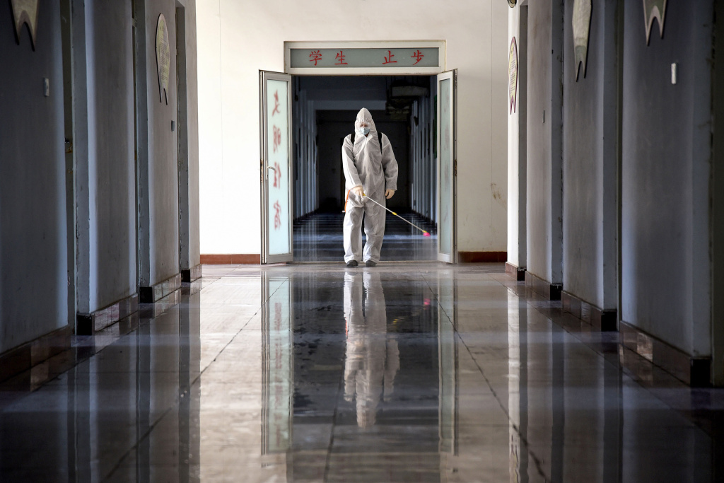 A staff member sprays disinfectant in the compounds of a school as it prepares to reopen after the term opening was delayed due to the COVID-19 coronavirus outbreak, in Handan in China's northern Hebei province.
