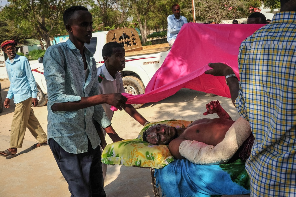 Two men carry a man who was injured when a truck bomb exploded in the center of Mogadishu on October 15, 2017.