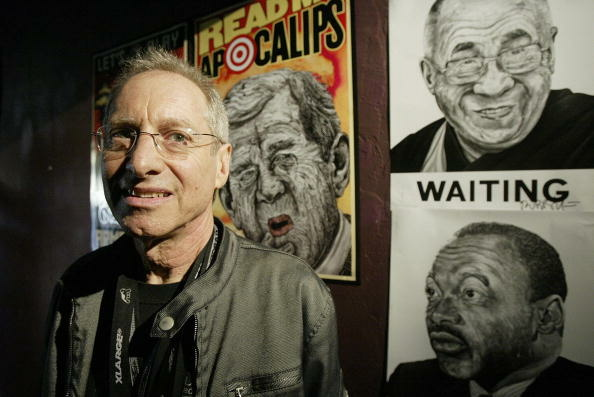 Artist Robbie Conal poses in front of so