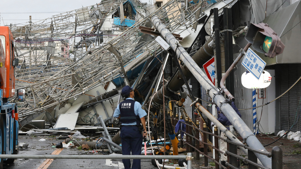 Damaged traffic boards and telecommunication relay poles are seen after they were brought down by strong winds caused by typhoon Jebi in Osaka on Tuesday.