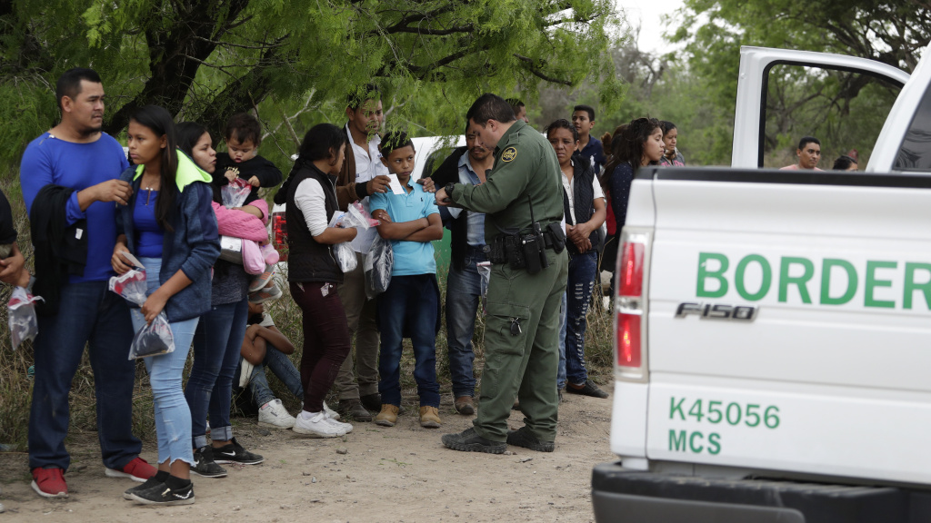 A Border Patrol agent checks the names and documents of families who crossed the nearby U.S.-Mexico border near McAllen, Texas. Immigration authorities say they expect the ongoing surge of Central American families crossing the border to multiply in the coming months.