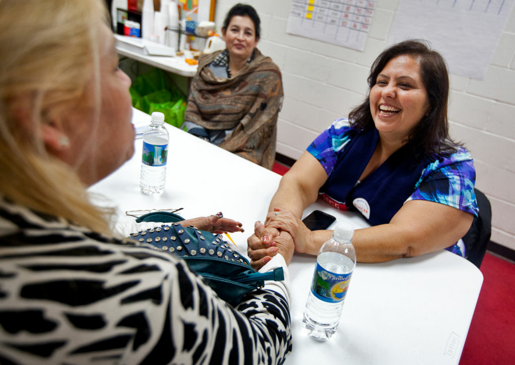 FILE - In a 2013 photo, LAUSD board member Monica Garcia speaks with campaign volunteer Blanca Dueñas at her East LA campaign office.
