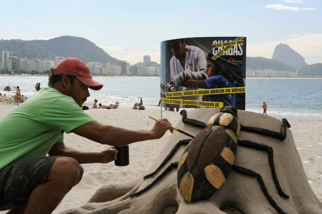 A beach artist gives the final touches to a sand sculpture of the insect that carries Chagas disease, at Copacabana Beach, Brazil.