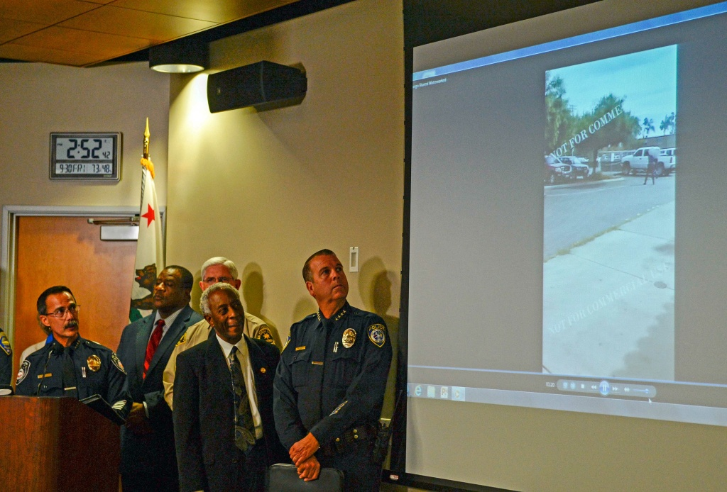 Authorities watch a video of the shooting scene at a news conference on Sept. 30, 2016, in El Cajon, Calif, that was held to address the killing of Alfred Olango, a Ugandan refugee shot by an El Cajon police officer. The El Cajon police department released video footage of the shooting at the news conference.