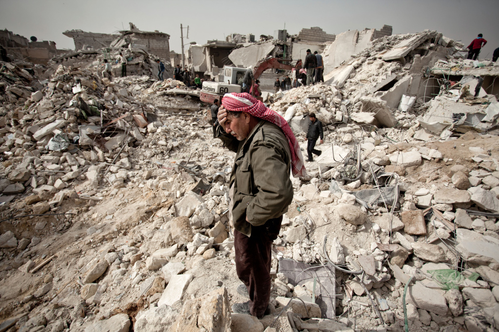 A Syrian man reacts while standing on the rubble of his house while others look for survivors and bodies in the Tariq al-Bab district of the northern city of Aleppo.