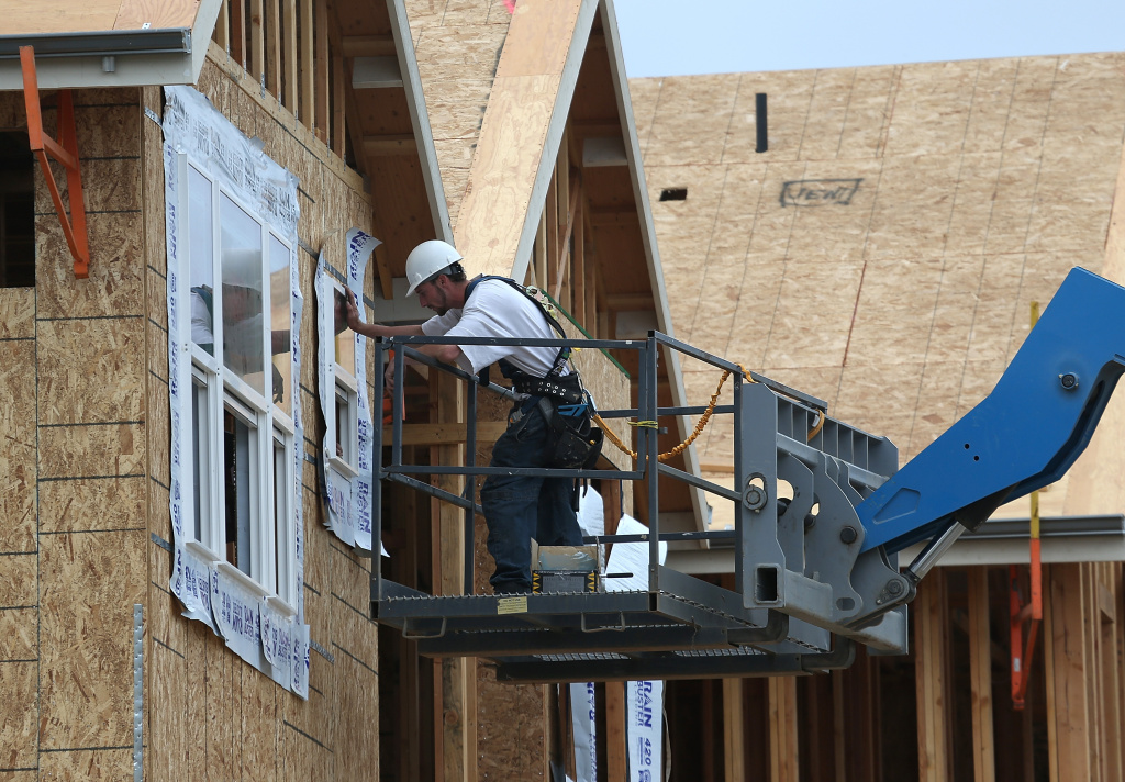 A construction worker installs a window in a new home at the Arbor Rose housing development  in San Mateo, California.