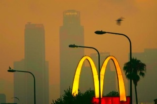 A McDonald's fast-food restaurant sign glows above the city skyline located in the Figueroa Corridor area of South Los Angeles, Los Angeles, California.