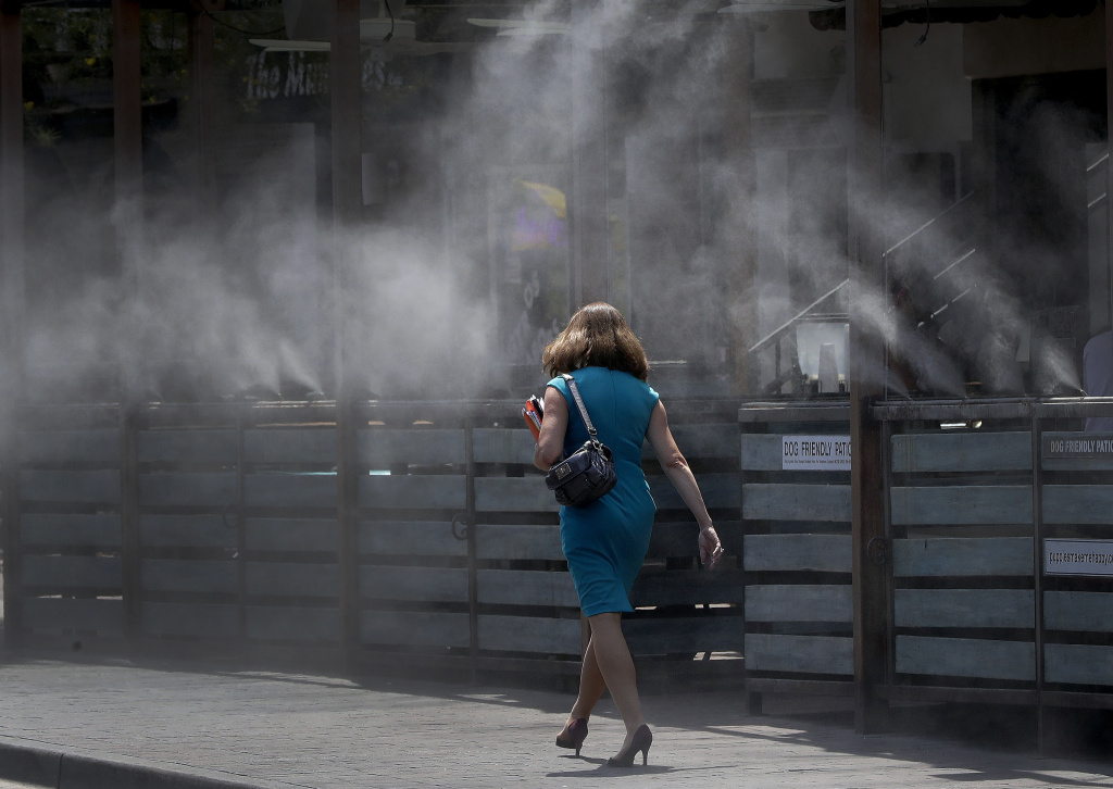 A woman walks along a row of misters on June 19, 2017 in Tempe, Ariz., when the temperatures were over 110 degrees.