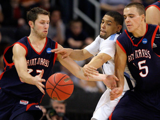 Villanova's Scottie Reynolds, center, fights through a screen by Saint Mary's Beau Levesque, right, to disrupt a dribble by Saint Mary's Mickey McConnell, left, during the first half of Saint Mary's 75-68 NCAA tournament victory.