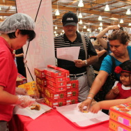 Costco customers in Alhambra reach out to grab a slice of a moon cake.