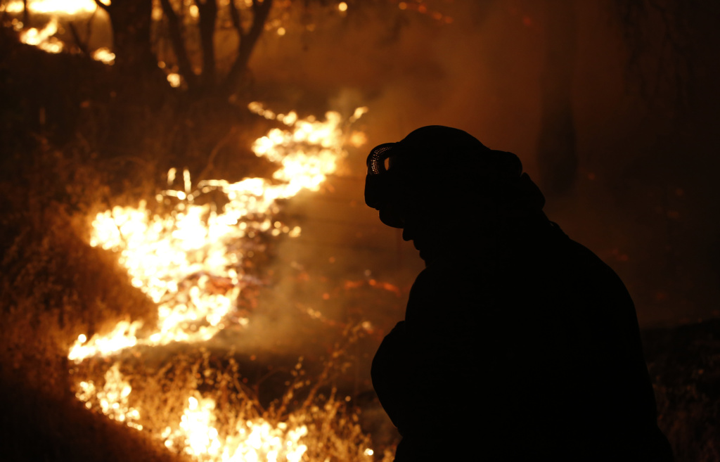 File: A firefighter turns his head from the flame of the Butte Fire burning near San Andreas on Sept. 11, 2015.
