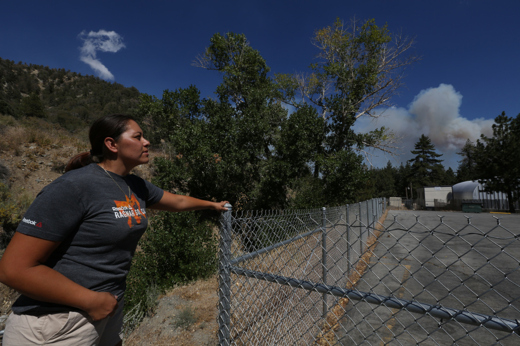 Nancy Martinez watches the plume of smoke from the Blue Cut fire approach Wrightwood, California on August 18th, 2016.