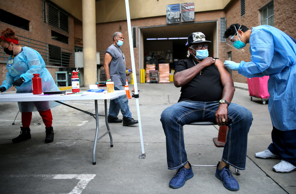 Tyrone Valiant, 73, receives a Band-Aid after being administered a dose of the Moderna COVID-19 vaccine by a healthcare worker outside the Los Angeles Mission located in the Skid Row community on February 10, 2021 in Los Angeles, California.