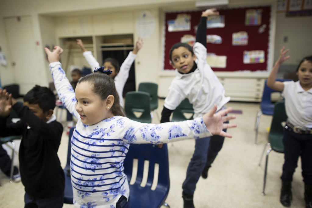 FILE: Children take part in a music class at Martin Luther King Elementary School in Compton on Dec. 5, 2014 as part of a program that brings arts education to high-poverty schools. A new report finds child poverty is unchanged despite the economic recovery.