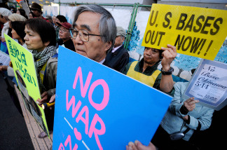 People hold banners in front of the Diet building in Tokyo on May 14, 2010 during a rally denouncing US bases in Okinawa, Japan's southernmost prefecture. Hundreds of people took part in the rally demanding withdrawal of US bases from Okinawa
