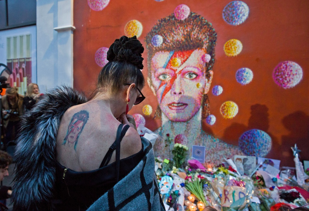A woman with a tatoo of David Bowie reacts as she pays her respects in front of the British singer, painted by Australian street artist James Cochran, aka Jimmy C.