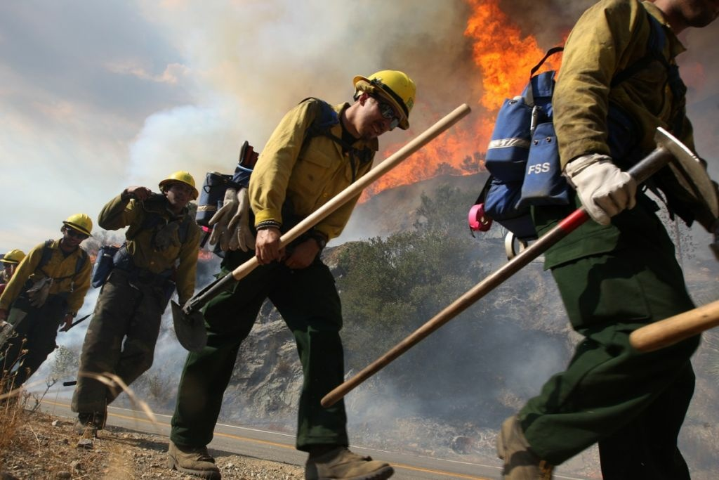 File photo: U.S. Forest Service firefighters walk near flames at the Williams fire in the Angeles National Forest on Sept. 4, 2012 north of Glendora. Workers continue to battle the wildfire and authorities estimate it to be fully contained by Thursday.