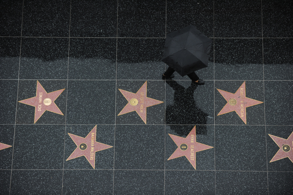 A tourist walks in the rain on the stars of the Hollywood Walk of Fame in Hollywood, California, on December 22, 2010. Downtown Los Angeles received one-third of its annual average rainfall in less than a week. As of midmorning yesterday, the rain gauge at the University of Southern California campus recorded 5.77 inches(14.6cm). AFP PHOTO / GABRIEL BOUYS (Photo credit should read GABRIEL BOUYS/AFP/Getty Images)