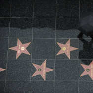 A tourist walks in the rain on the stars of the Hollywood Walk of Fame in Hollywood, California, on December 22, 2010.
