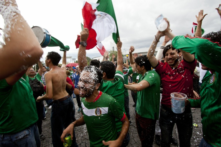 Mexican fans celebrate after the Mexico vs Croatia FIFA World Cup football match, in the 'Minerva' fountain in Guadalajara City, Mexico on June 23, 2014. Mexico won 3-1 and qualified for the knockout round.
