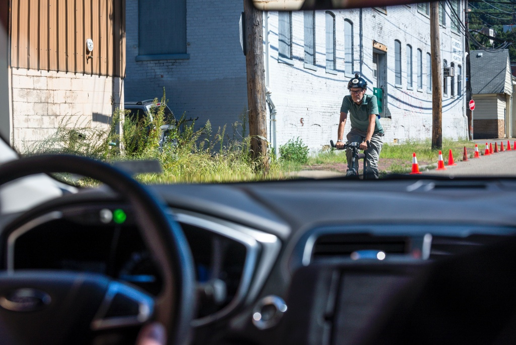 A biker passes a pilot model of the Uber self-driving car on September 13, 2016 in Pittsburgh, Pennsylvania.