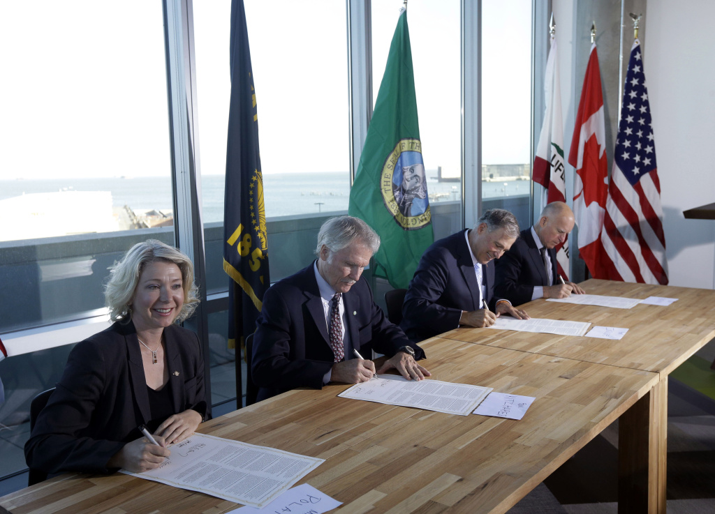 From left, Mary Polak, environment minister of British Columbia, representing British Columbia premier Christy Clark, Oregon Gov. John Kitzhaber, Washington Gov. Jay Inslee and California Gov. Jerry Brown sign an agreement to collectively combat climate change on Monday, Oct. 28, 2013, in San Francisco. The group will work together to coordinate efforts with the hope of stimulating a clean-energy economy in a region with a combined gross domestic product of $2.8 trillion.