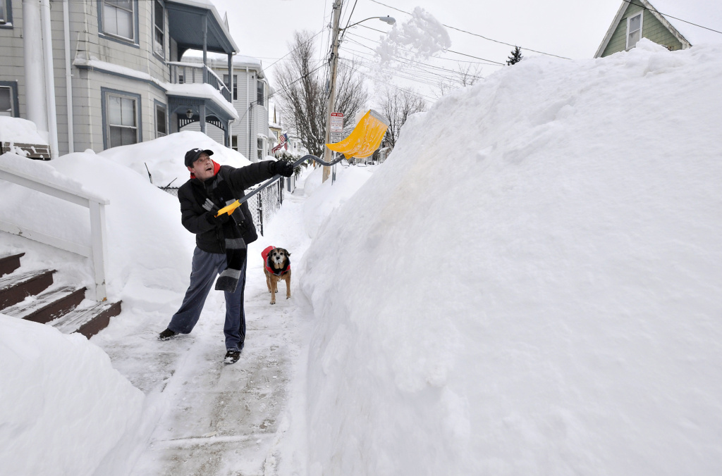 File: In this Feb. 10, 2015 file photo, Lee Anderson adds to the pile of snow beside the sidewalk in front of his house in Somerville, Mass., as his dog Ace watches. It may be hard to believe for a country that's shivering from Maine to Miami, but 2014 has gotten off to a rather toasty start. Meteorologists said that last month was the second warmest January on record globally, behind 2007, with temperatures 1.4 degrees above 20th century average. The National Oceanic and Atmospheric Administration calculated that the United States in January was 2.9 degrees warmer than normal, making it the 24th warmest January since 1880.